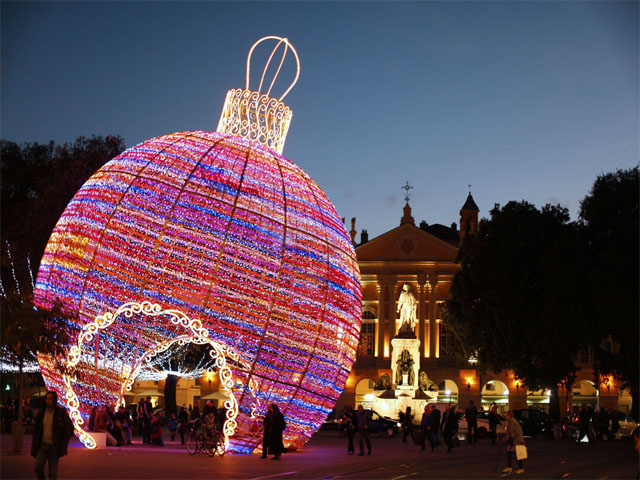 People walk by a giant christmas ball displayed in Nice, southeastern France, on December 4, 2013. AFP PHOTO / VALERY HACHEVALERY HACHE/AFP/Getty Images ORG XMIT: